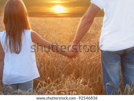 Father with his daughter at sunset in barley field - stock photo