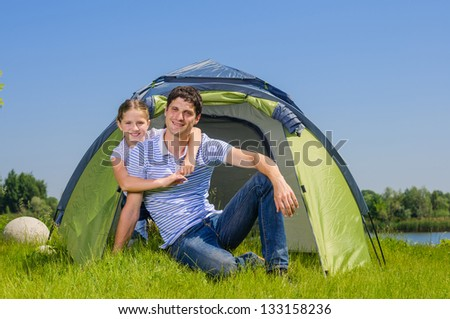 Father with his daughter resting on the grass and camping with tent - stock photo