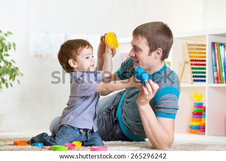 father with his kid boy playing together at home - stock photo