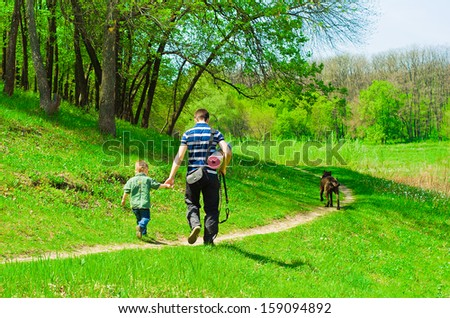 Father with his son and dog for a walk in the forest