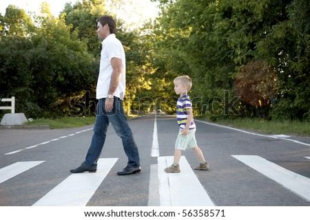 father with his son cross crosswalk - stock photo