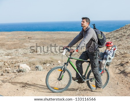 Father with his son having a weekend excursion on bike on a summer day in beautiful landscape - stock photo
