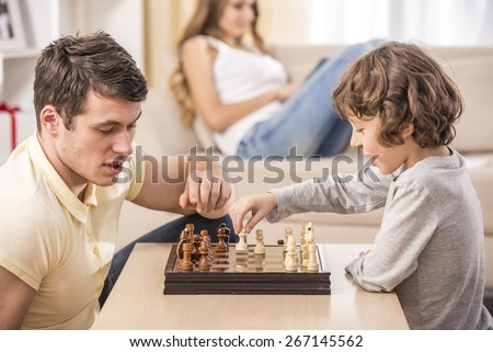 Father with his son playing chess in living room. Mother using a tablet on the couch.