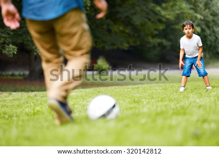 Father with his son playing football on the green grass in the park. Boy is very excited.