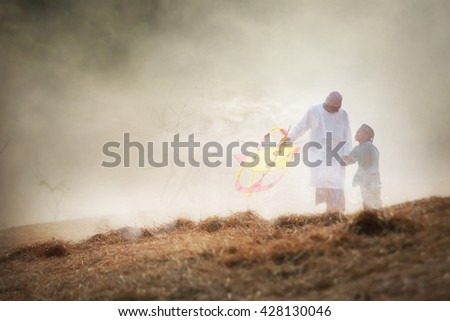 Father with his son playing with kite.Blurry scene of morning with the mist. Muslim Family Vacation. - stock photo
