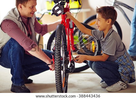 Father with his son repairing a bike together - stock photo