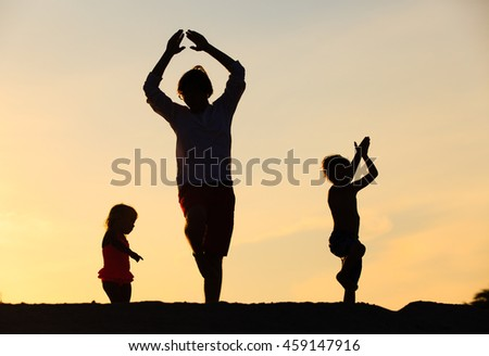 father with kids silhouettes having fun at sunset