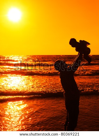 father with little baby on the sea - stock photo