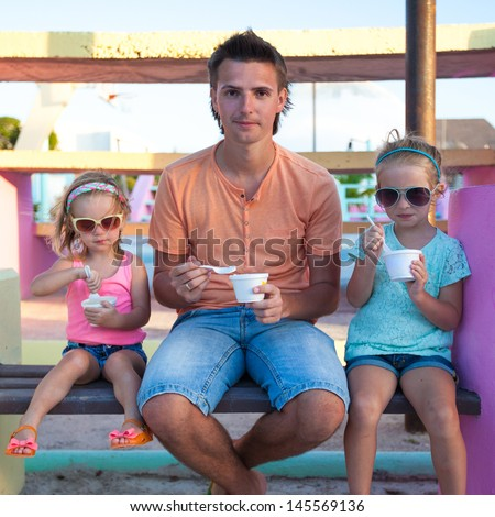 Father with little cute  daughters eating ice-cream outdoor - stock photo