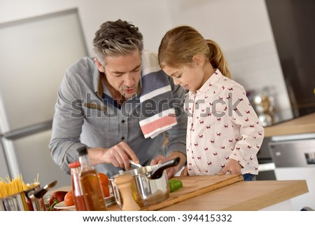 Father with little girl cooking together in kitchen - stock photo