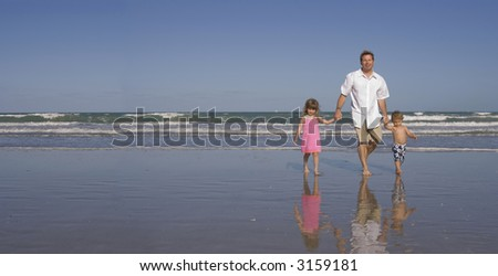 Father with son and daughter walking on a beach - stock photo