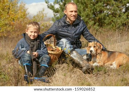 Father with son and pet resting on the forest glade after mushroom picking - stock photo
