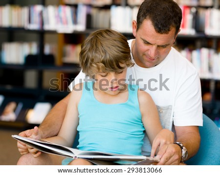 Father with son in library with books - stock photo