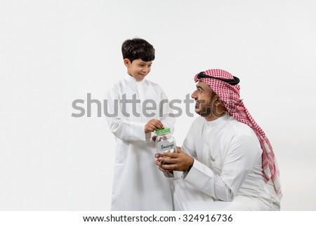 Father with son inserting coin in money box - stock photo
