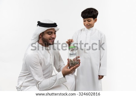 Father with son inserting money in money box - stock photo