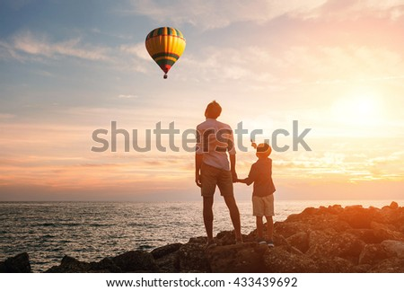 Father with son look on the balloon on the sea coast - stock photo