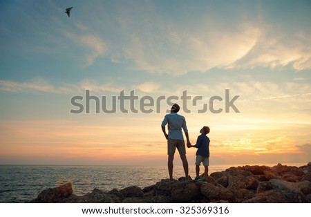 Father with son on the sea coast in sunset time - stock photo