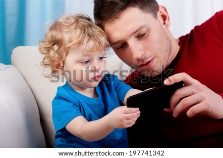 Father with son playing on the phone - stock photo