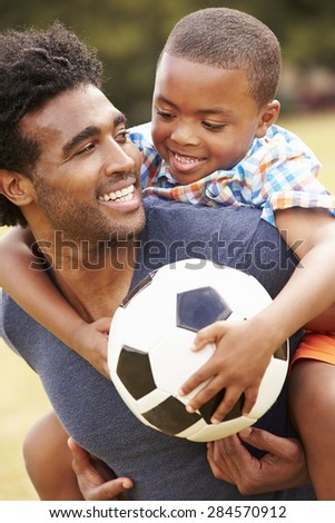 Father With Son Playing Soccer In Park Together - stock photo