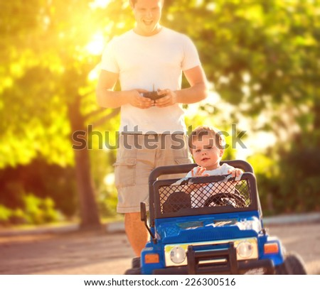 Father with son playing with toy car - stock photo