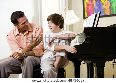 Father with teenage son at home talking together - stock photo