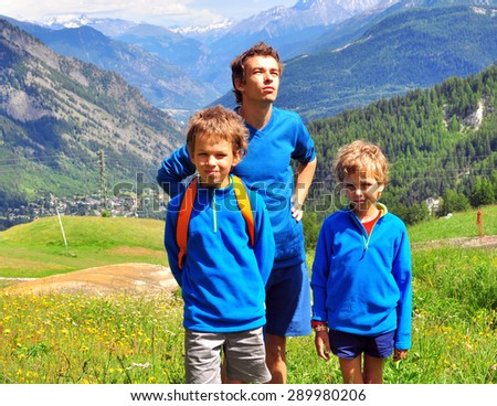 Father with two kids in mountains on summer