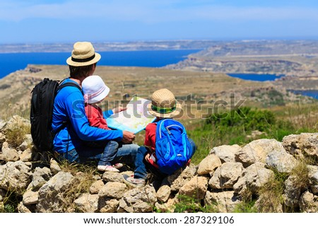 father with two kids looking at map in mountains, family travel