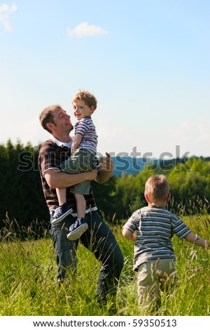 Father with two little boys playing in the grass on a summer meadow carrying one of the kids