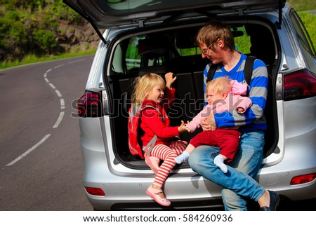 father with two little kids travel by car in nature