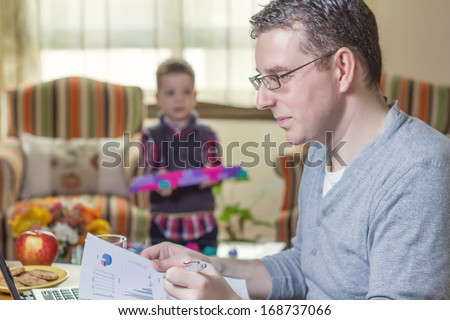 Father working hard in home office with notebook and his boring son playing on the background - stock photo