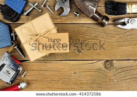 Fathers Day gift box with tag and corner border of tools and ties on a rustic wood background - stock photo