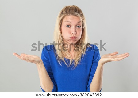 fatigue or boredom concept - frustrated young blond woman puffing her cheeks out for resignation and disillusion with hand gesture,studio shot - stock photo