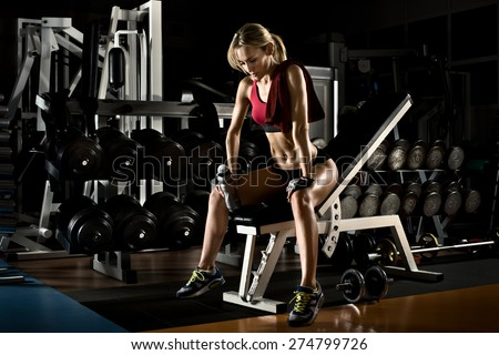 fatigued beautiful girl bodybuilder,  rest post  exercise with  weight - stock photo