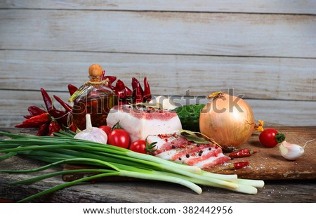 Fatty bacon with vegetables and olive oil on chopping board - stock photo