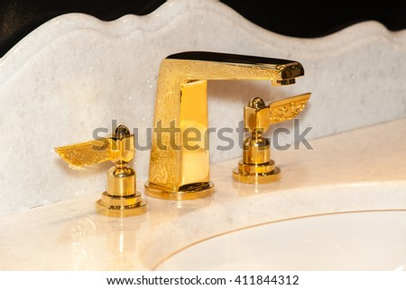 Faucet of gold color in bathroom interior - stock photo