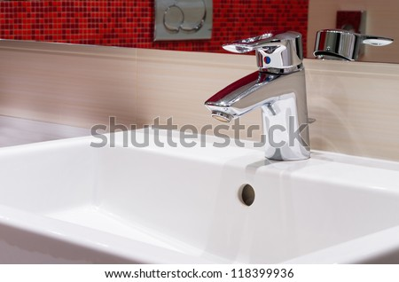 faucet on white sink in modern bathroom - stock photo