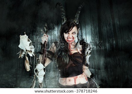 Faun sorceress with big horns in a forest - stock photo