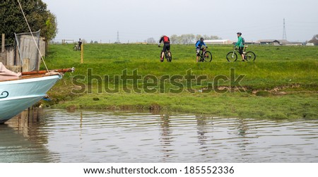 FAVERSHAM, KENT/UK - MARCH 29 : Cyclists pause to look at the river Swale in Faversham Kent on March 29, 2014. Unidentified people.