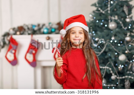 Favorite holiday. Overjoyed delighted little girl wearing hat and expressing joy and having fun near Christmas tree - stock photo