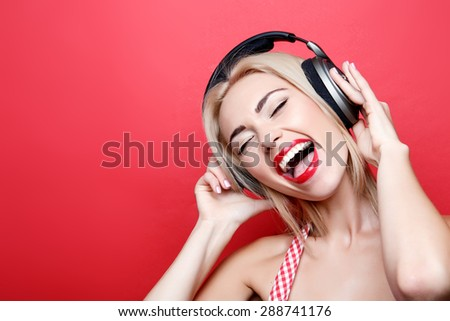 Favorite song. Smiling young blond-haired girl sloping her head and listening to music while standing on isolated red background - stock photo