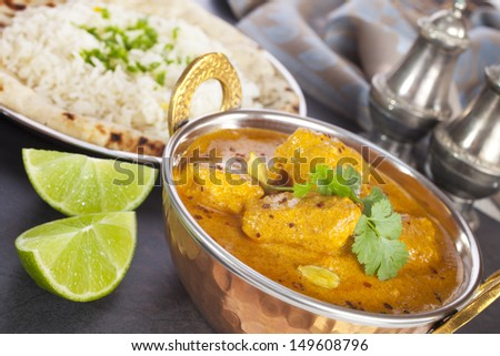 Favourite Indian meal, butter chicken with basmati rice, naan bread and lime. - stock photo