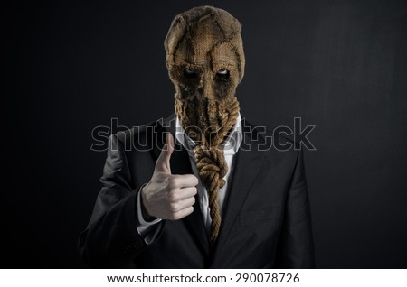 Fear and Halloween theme: a brutal killer in a mask on a dark background in the studio - stock photo