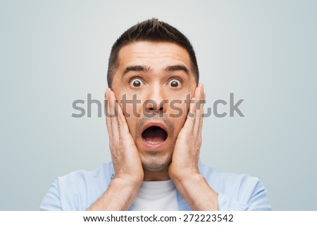 fear, emotions, horror and people concept - scared man shouting and touching his face over gray background - stock photo