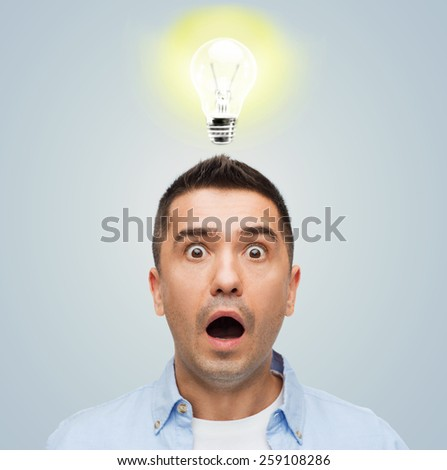 fear, emotions, horror, idea and people concept - scared man with big eyes and open mouth over gray background with lighting bulb - stock photo