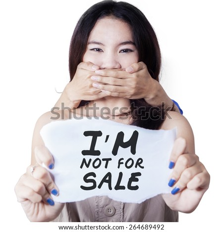 Fear teenage girl showing paper with a text of not for sale, isolated over white background - stock photo