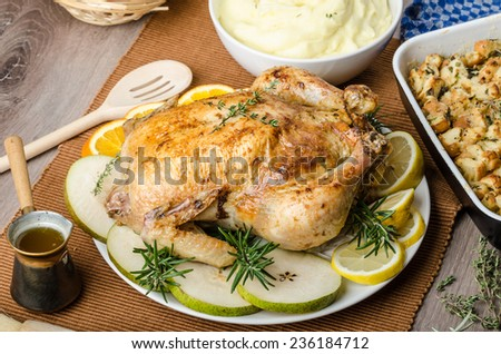 Feasting - stuffed roast chicken with herbs, mashed potatoes with oregano leaves and homemade stuffing with herbs, freshly squeezed orange juice, fresh fruits and old shool sauce boat - stock photo