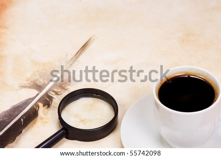 feather and magnifying glass at table - stock photo