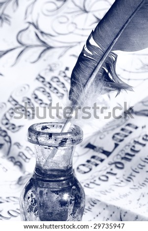 Feather in inkwell on ancient parchment manuscript / colored blue - stock photo
