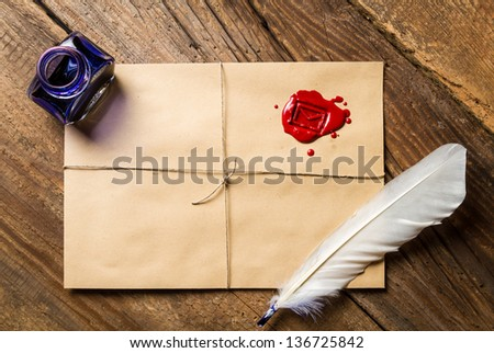 Feather on envelope with red sealant and inkwell - stock photo