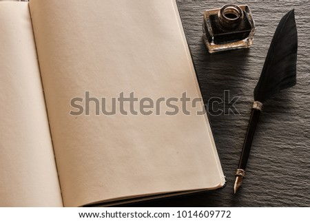 Feather pen and blank notebook page over slate background
